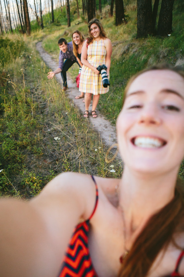 A woman takes a selfie in the forest with her friends