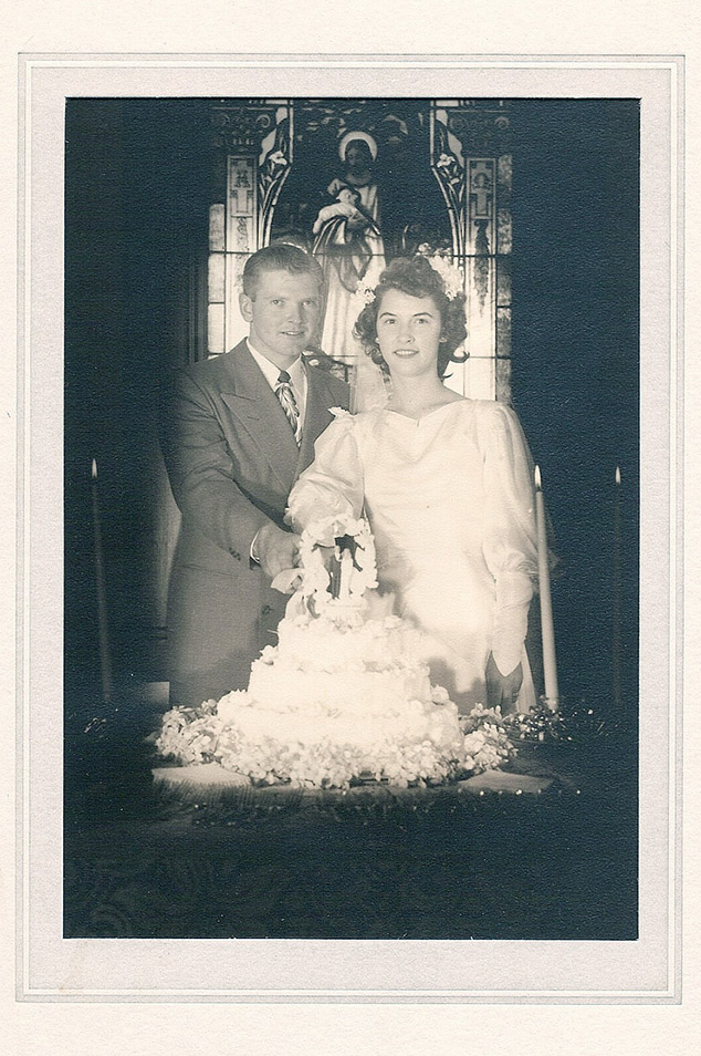 An old black and white wedding portrait of a bride and groom cutting their cake