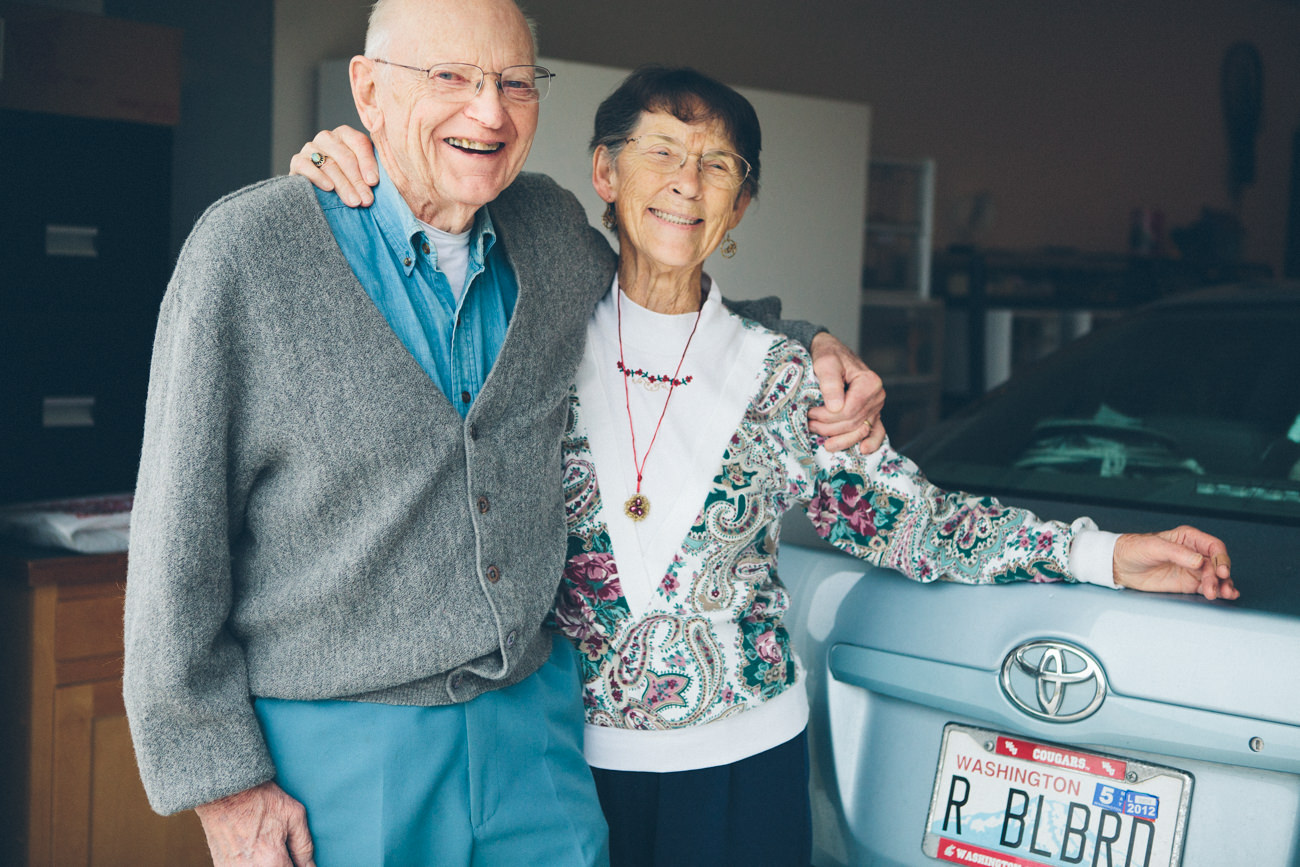 A husband and wife in their 80s laugh and hug as they stand next to their car